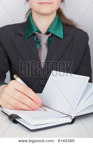 Businesswoman Writes Down Plans In Notebook