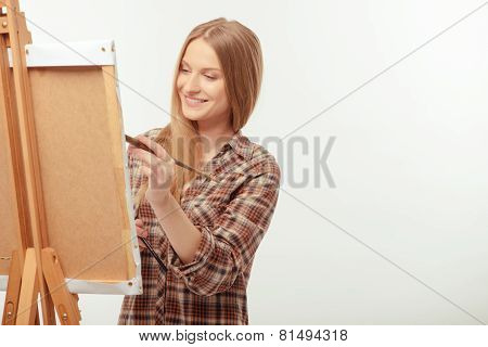 Young beautiful artist posing with a drawing easel