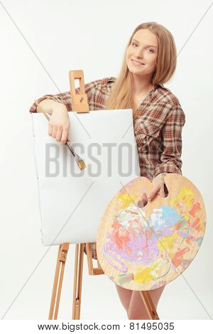 Young beautiful artist posing with a drawing easel and palette