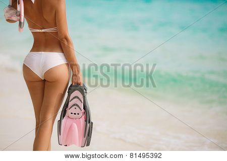 A woman with a beautiful figure near the ocean with snorkeling equipment.