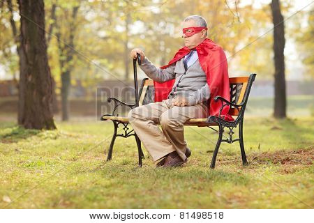 Sad senior in superhero outfit sitting in park on a wooden bench