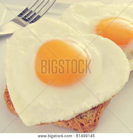 closeup of some heart-shaped fried eggs served on toasts, with a filter effect