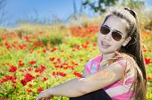 image of windflowers  - Teenage girl with braces on her teeth in a field of wild red anemone coronaria  - JPG