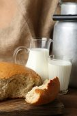 image of milk products  - Retro can for milk with fresh bread and glass of milk on wooden background - JPG