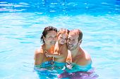 pic of swimming pool family  - Happy family in swimming pool with baby girl in summer vacation - JPG