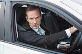 picture of driver  - Unsmiling businessman in the drivers seat in his car - JPG