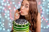 stock photo of finger-licking  - Beautiful girl tasting happy birthday cake by licking her finger with cream on festive light background - JPG