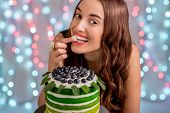 pic of finger-licking  - Beautiful girl tasting happy birthday cake by licking her finger with cream on festive light background - JPG