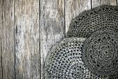 stock photo of doilies  - Grunge style decoration with old handmade crochet doilies over wooden background - JPG