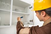 picture of pesticide  - Pest Control Worker With Flashlight Checking Kitchen Shelf - JPG