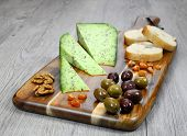 image of collate  - Olives provencal solid cheeses plate walnuts and slices of baguette  - JPG