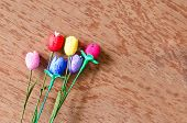 picture of cocoon  - colorful artificial tulips flower made from silk cocoon on plywood background - JPG