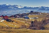 pic of hamlet  - Peaceful sunny rural landscape with alpine hamlet and wide grasslands in Pestera village Brasov county Romania - JPG