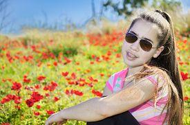stock photo of windflowers  - Teenage girl with braces on her teeth in a field of wild red anemone coronaria  - JPG