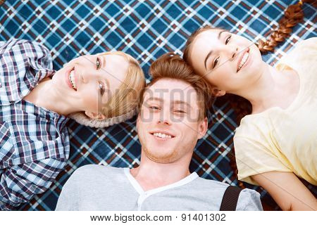 Happy young people lying on cover