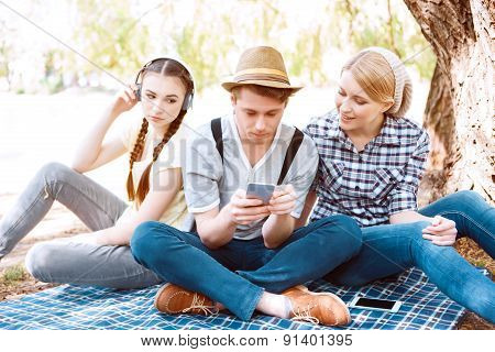 Young people sitting on cover at picnic