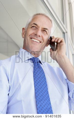 Mature Businessman Standing Outside Modern Office Talking On Phone