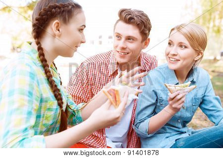 Young people sitting on cover and holding sandwiches