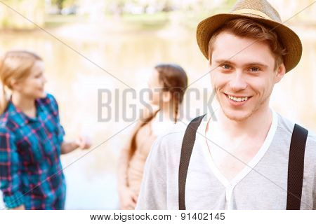 Handsome man with hat in park.