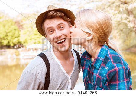 Pretty lady giving cheek kiss to his boyfriend