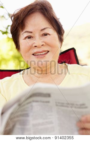 Senior Asian woman reading outdoors