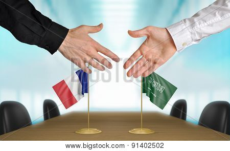 France and Saudi Arabia diplomats agreeing on a deal