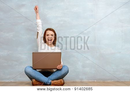Woman sitting cross-legged pointing up with her arm