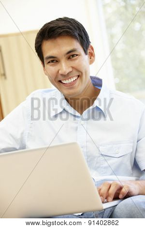 Asian man using laptop at home