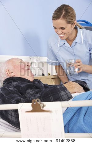 Nurse giving glass of water to senior man in hospital