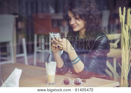 Brunette Beautiful Stylish Caucasian Woman In Casual Outfit On A Walk On European City Street Sittin