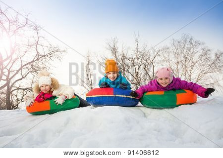 Row of children sliding down on the tubes