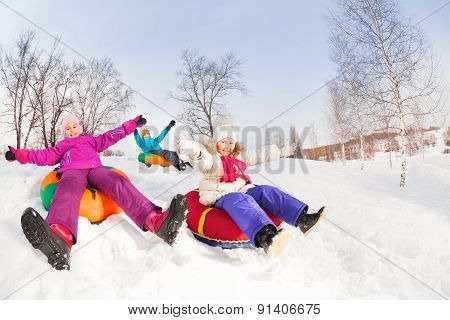 Happy girls and boy slide on colorful tubes
