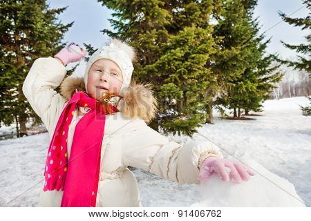 Cute girl ready to throw snowball during day