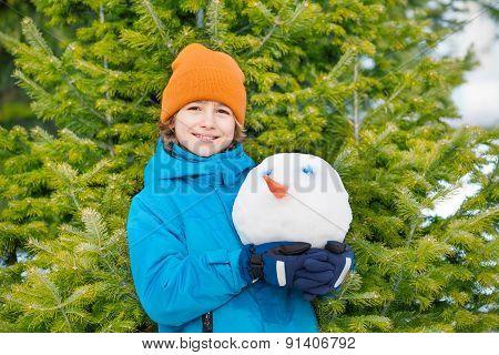 Portrait of smiling kid holding snowman's head
