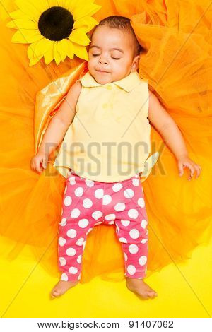 Sweet African baby sleeping on sunflower cloth