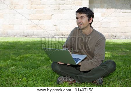 man sitting on the grass working with a laptop
