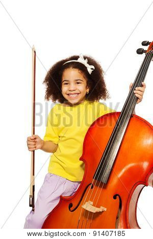 Cheerful African girl holds cello with fiddlestick