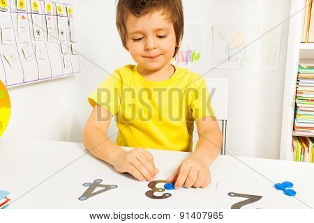 Smiling boy put coins on numbers learning count