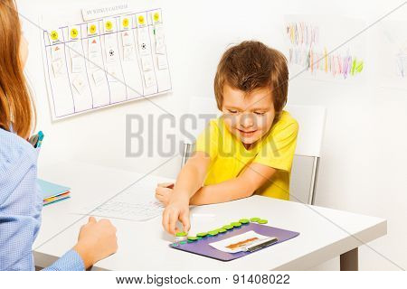 Smiling boy puts coins during developing game