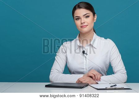 Beautiful girl tv newscaster is reporting sitting at the table