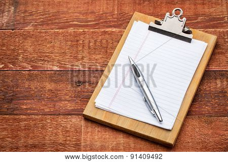 small wooden clipboard with blank paper and pen against rustic barn wood with a copy space