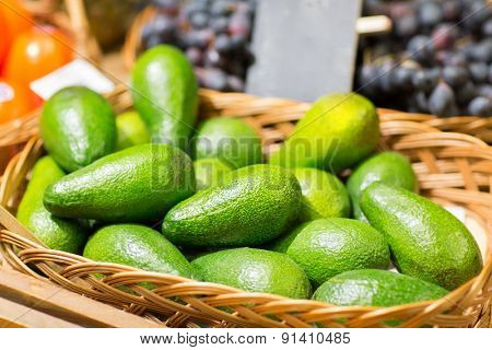 sale, shopping, vitamin c and eco food concept - ripe avocado in basket at food market
