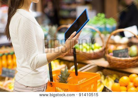 sale, shopping, consumerism and people concept - close up of young woman with food basket and tablet pc computer in market
