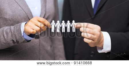 business and office concept - businessman and businesswoman holding paper team in office