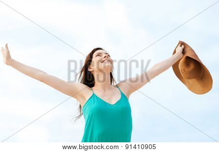 summer holidays and vacation concept - girl with hands up on the beach