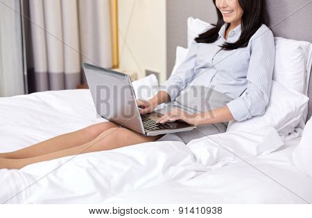 business trip, people and technology concept - smiling businesswoman with laptop computer typing in bed at hotel