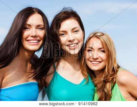 summer holidays and vacation concept - girls walking on the beach