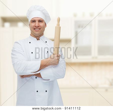 cooking, profession and people concept - happy male chef cook holding rolling pin