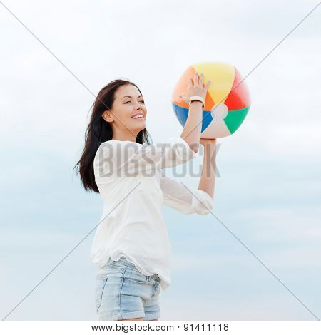 summer holidays, vacation and beach activities concept - girl with ball on the beach
