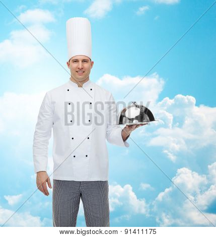 cooking, profession and people concept - happy male chef cook holding cloche over blue sky with clouds background